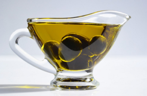 Pure olive oil in a cup with olives
