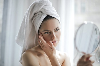Woman observing facial skin in mirror after shower