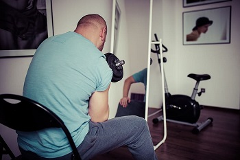 man training and weightlifting at home gym
